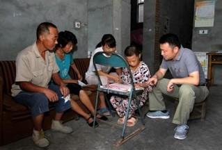 290万扶贫干部中的一员,在皖西北临泉县刘桥村(现已改名为刘桥社区)挂职工作的颜亮亮(右一),正在走访村民。(受访者供图)