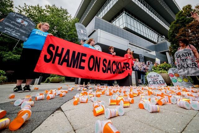 美国抗议者荟萃在一家阿片类药物生产商总部外 图源:美媒