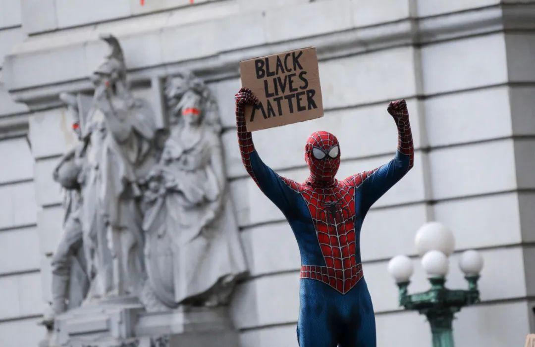 """6月30日,别名打扮成""""蜘蛛侠""""的抗议者在美国纽约市政厅附近手举写有""""暗人的命也是命""""的标语。新华社记者王迎摄"""