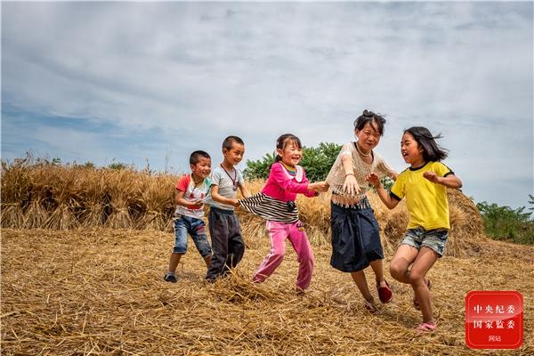 收获季节,孩子们在田间地头快乐地玩起了游戏。(浙江省浦江县纪委监委供 马黎晶 摄)