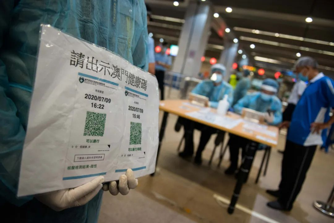9月29日,工作人员在澳门关闸口岸提示抵澳人士出示澳门健康码。图片来源:新华社张金加 摄