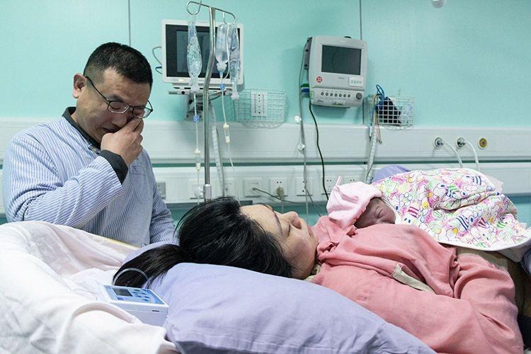 """2020年1月1日0时20分,北京妇产医院分娩室生产室,荀女士产下该院首个""""20后""""宝宝,父亲于先生忍不住擦拭眼泪。 新京报记者 陈婉婷 摄"""