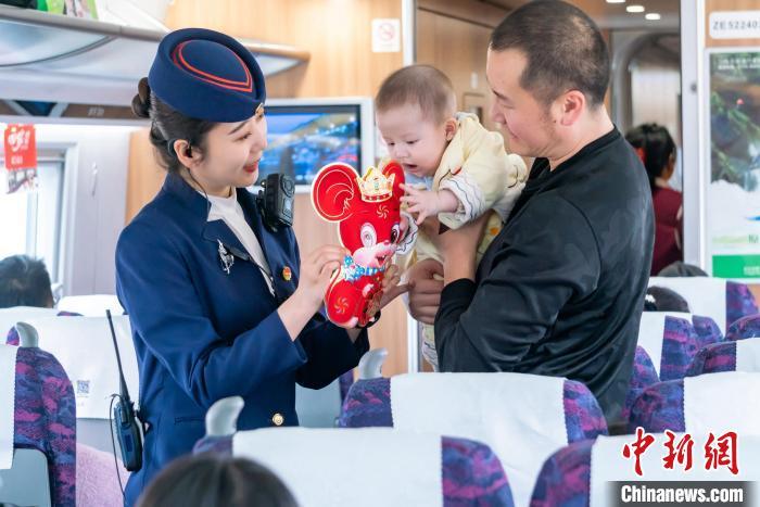 乘务人员向幼乘客送上鼠年幼礼物。 方正 摄
