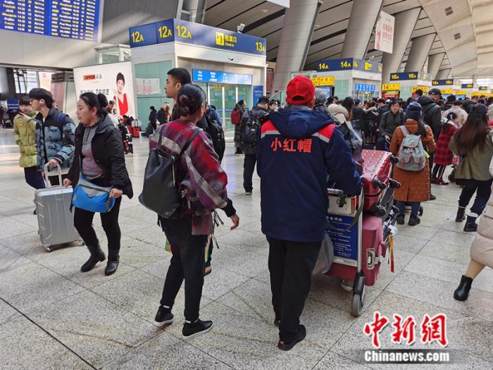 """1月10日,北京南站内,""""幼红帽 """"协助旅客运送走李。 中新网记者 张尼 摄"""