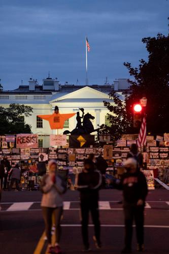 10月31日薄暮在美国华盛顿拍摄的白宫,铁栅栏上挂满抗议标语。新华社记者刘杰摄
