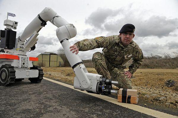 原料图片:英陆军士兵与排爆机器人相符影。(英国防部官网)