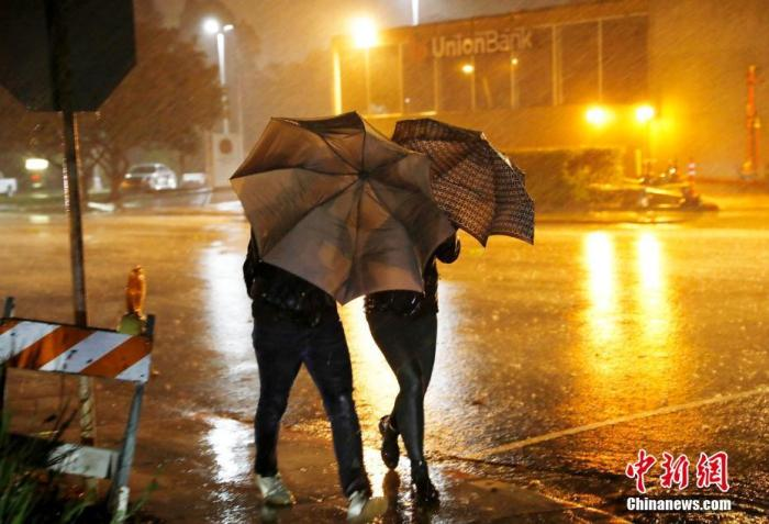 原料图:美国民多在狂风暴雨中前走。中新社记者 刘关关 摄
