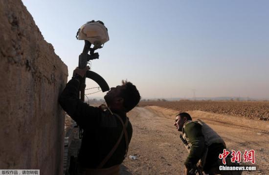 资料图:一名伊拉克士兵用头盔作为诱靶,来确定极端组织人员的位置。