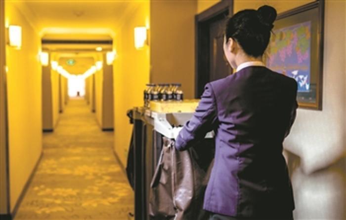 某五星级酒店房间保洁员推着工作车赶往下一间客房。 李润钊 摄