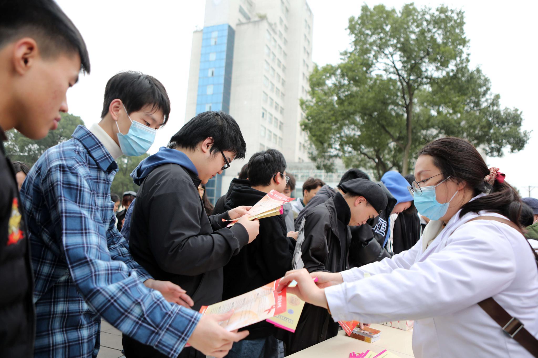 △11月30日 重庆 医务人员给大学生宣传艾滋病科普知识图源:视觉中国