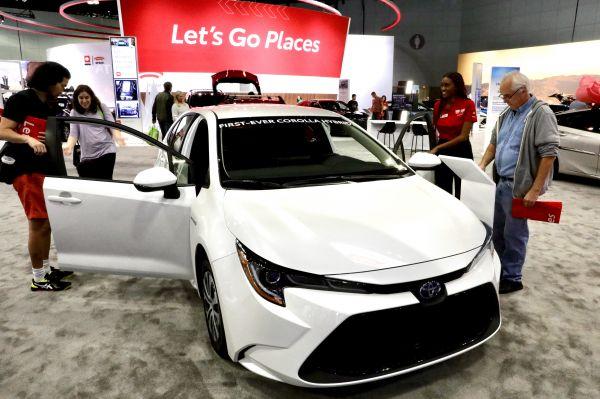 在美国洛杉矶,人们参不悦目新一代丰田花冠汽车。(新华社)