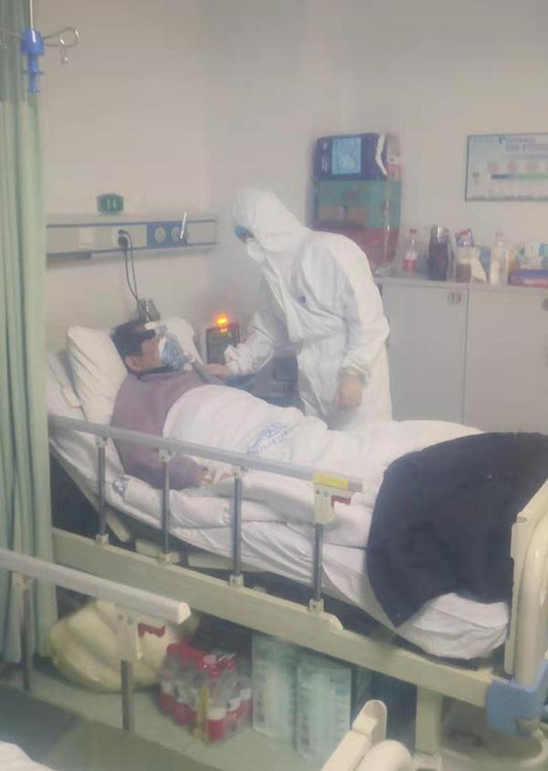 """汤浩在""""呼三""""病区查望重症肺热患者。(隔防护罩拍摄)"""