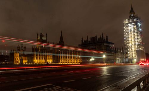 12月23日,车辆从英国伦敦的议会大厦前驶过。新华社记者张铖摄
