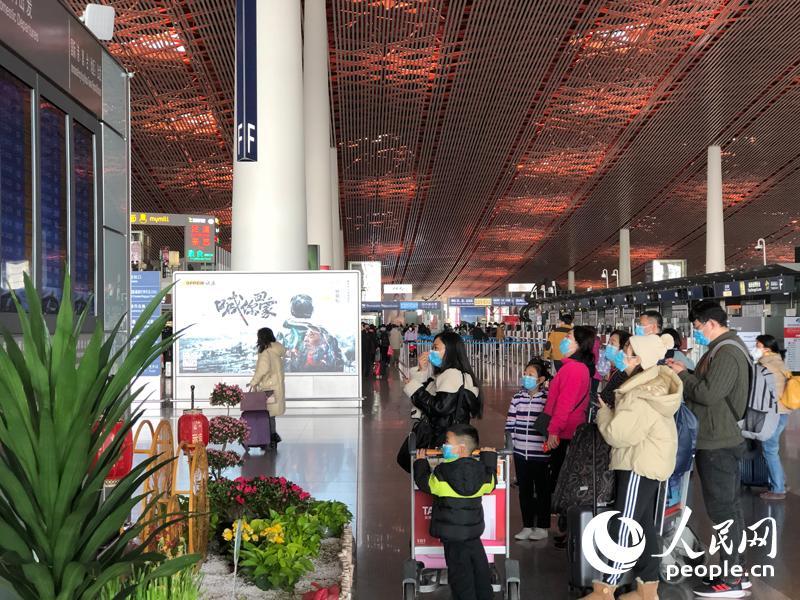 在首都机场T3航站楼,绝大多数旅客都已自觉配戴口罩。人民网记者 崔东摄