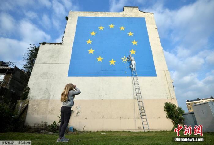 原料图:当地时间2017年5月7日,英国多佛,别名街头艺术家班克西创作了一幅画,画面中别名工人正从欧盟1星旗帜上抹失踪一颗星,寓意着英国将脱离欧盟。