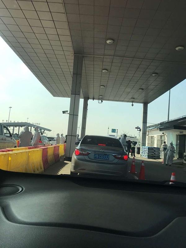 崇启大桥收费站医护工作者给过路车辆人员测体温,受访者张女士供图