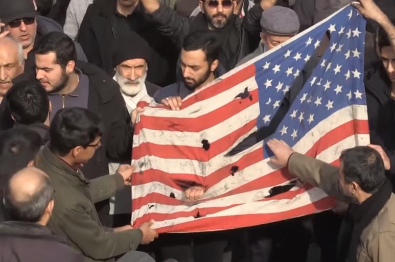 抗议者撕毁美国国旗(来源:《卫报》)