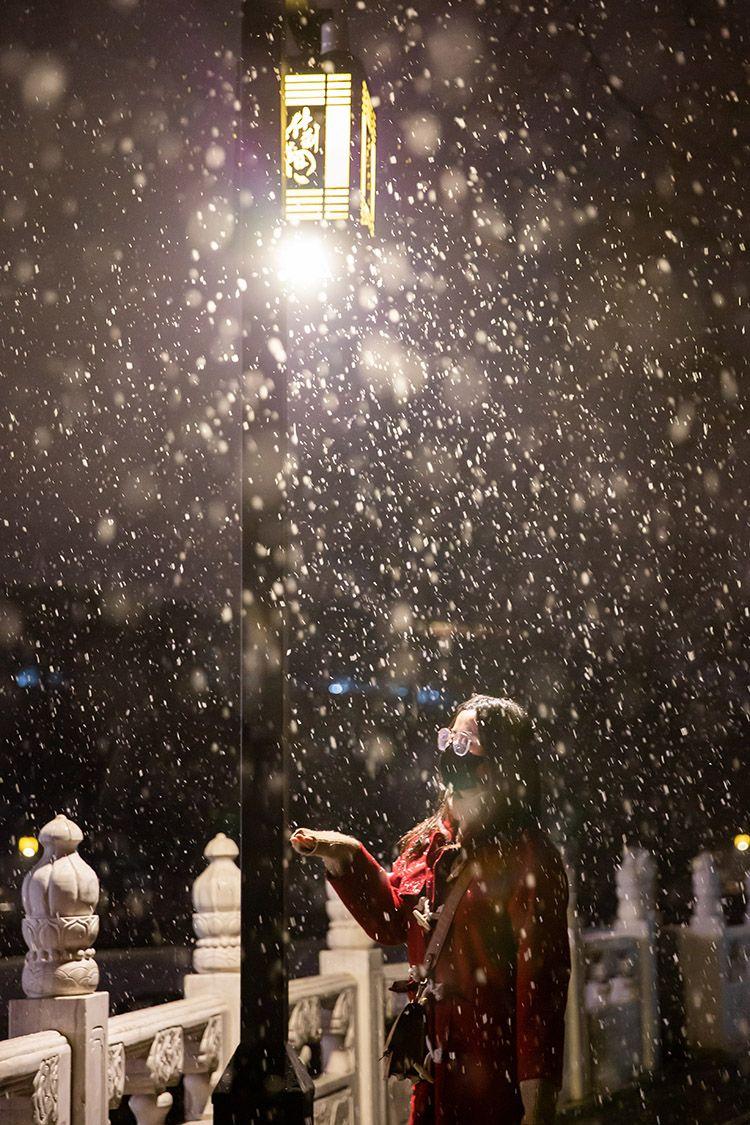 什刹海岸边,路灯的映照下,大片的雪花飘落。