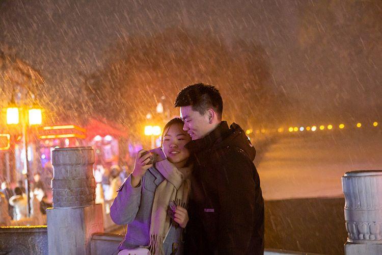 银锭桥上,一对情侣在雪中合影。