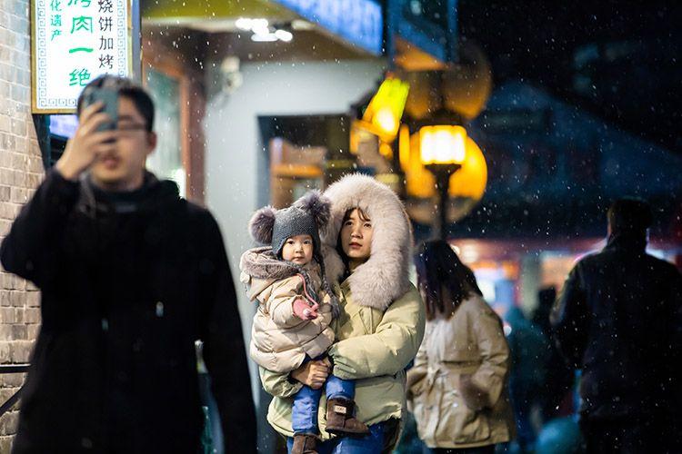 烟袋斜街,家长在雪中抱紧孩子。