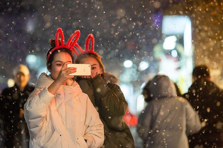 烟袋斜街,一对女青年在雪中合影。