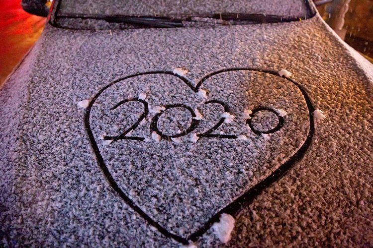 """什刹海,汽车被白雪覆盖,人们在上面写下""""2020""""。"""