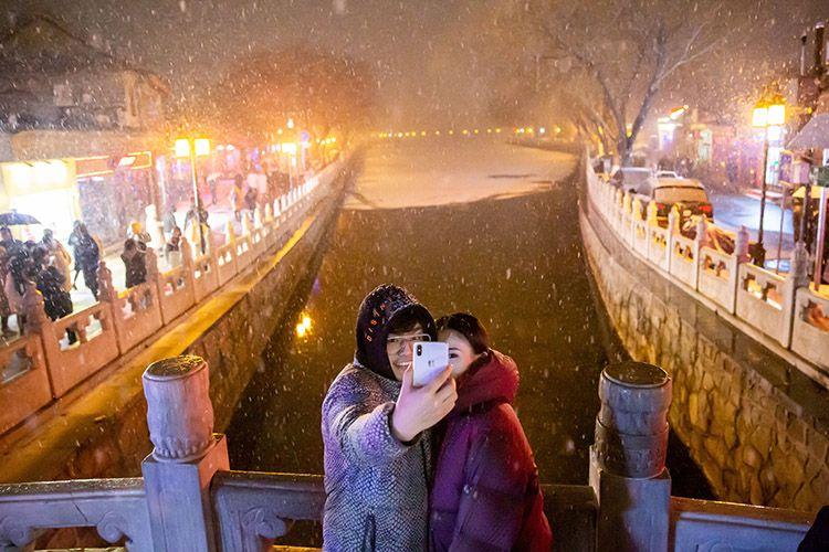 银锭桥上,游客在雪中留影。