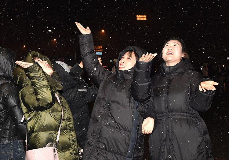 朝阳区合生汇门前,市民用手接着雪花。