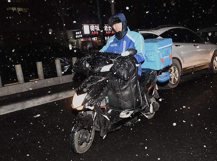 朝阳区东九路,外卖小哥冒雪送餐。
