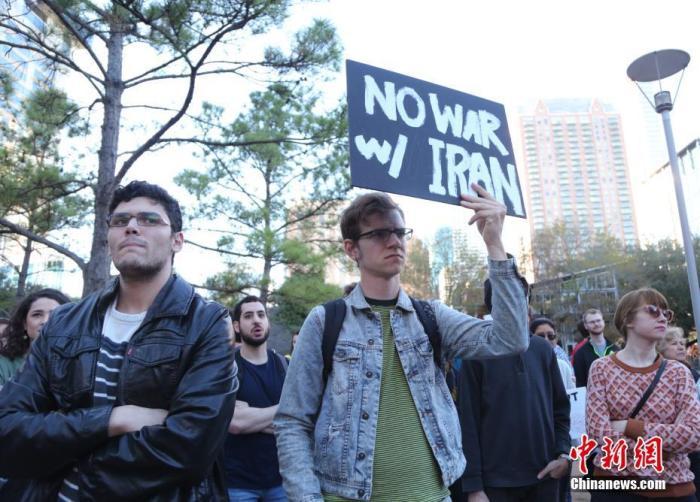 """当地时间1月5日,美国石油重镇息斯敦的民多举走逆战集会,训斥美军炸物化伊朗军官卡西姆·苏莱曼尼,指斥美军向中东地区添派约3千名士兵的决定。图为集会民多手持""""偏差伊朗发首搏斗""""的标语。 中新社记者 曾静宁 摄"""