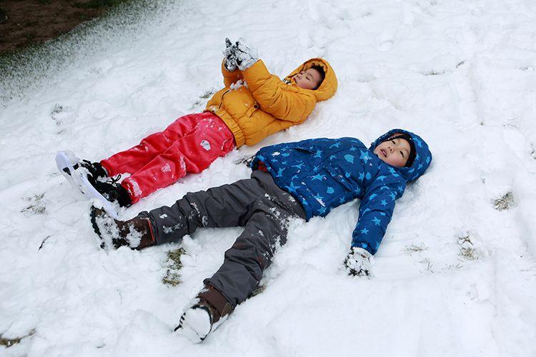 幼至交躺在雪地上抬看天空。
