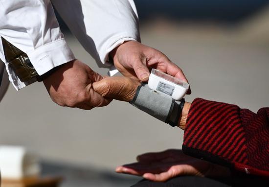 在广西柳州市鹿寨县四排镇江南村,一位村医在给村民量血压。新华社记者黄孝邦/摄