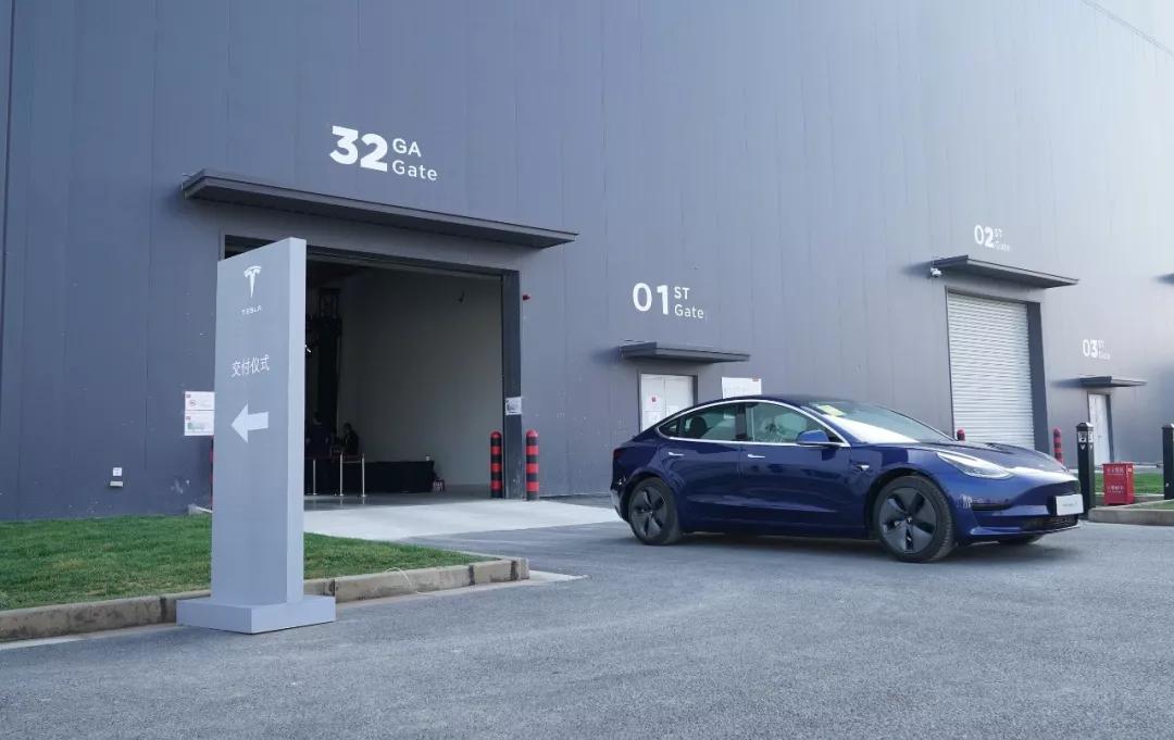 12月30日,一辆完成交付的特斯拉Model 3汽车驶出工厂车间(新华社记者 方喆 摄)