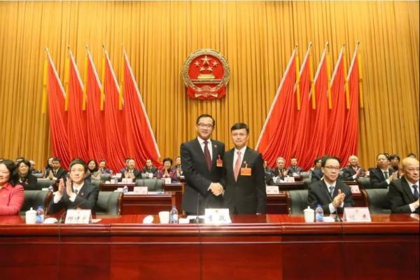 区委书记李政与缪京握手,表示祝贺