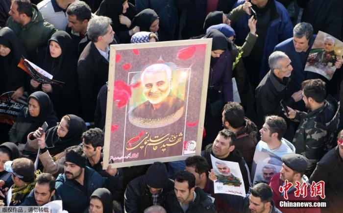 当地时间1月6日,成千上万的伊朗民众走上德黑兰街头,向被美军击杀的高级军官苏莱曼尼表示敬意。图为追悼会上民众高举苏莱曼尼的照片。