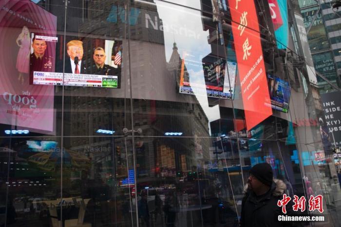 当地时间1月8日,纽约时代广场的电视直播特朗普电视讲话吸引路人驻足观看。 中新社记者 廖攀 摄