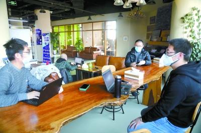 昨天,中关村创业大街的片面注册企业不息最先复工。在孵化平台,几位创业者佩戴口罩,拉开座位间距开会商议做事。本报记者 饶强摄