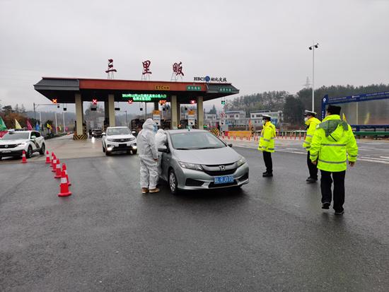 湖北黄冈三里畈镇医护人员与民警一起在高速路口对入境车辆驾乘人员体温检测。三里畈镇防控指挥部提供