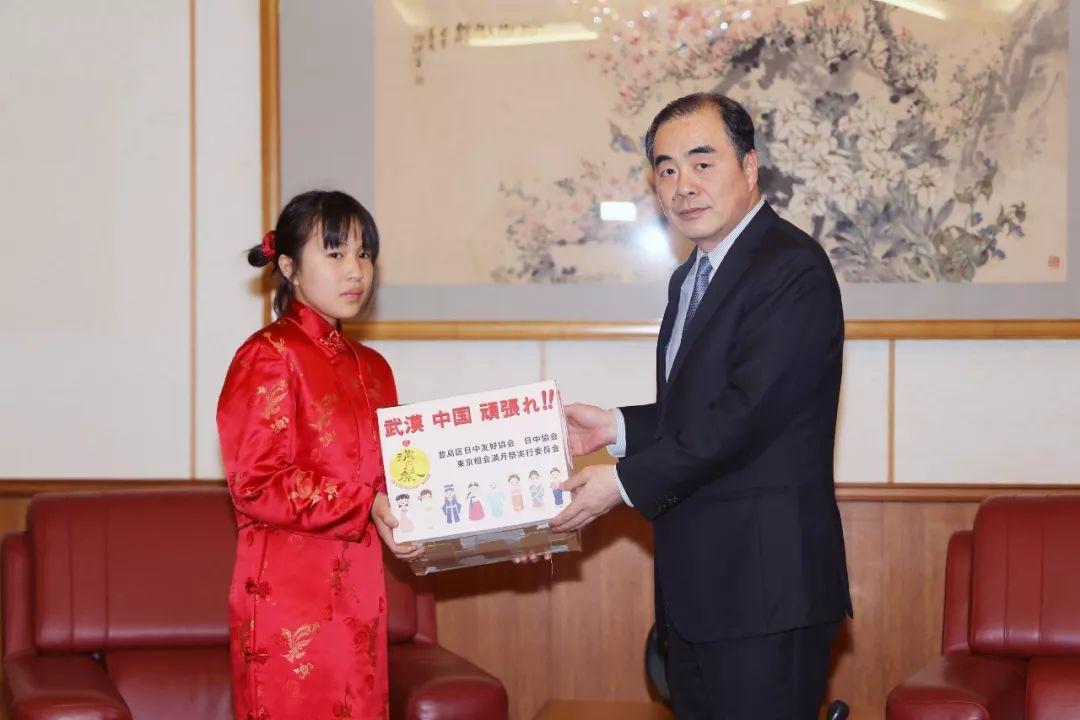 2月13日,在日本东京中国驻日本大使馆,为中国武汉募捐的旗袍女孩(左)将募捐到的善款交给中国驻日本大使孔铉佑。新华社记者杜潇逸 摄