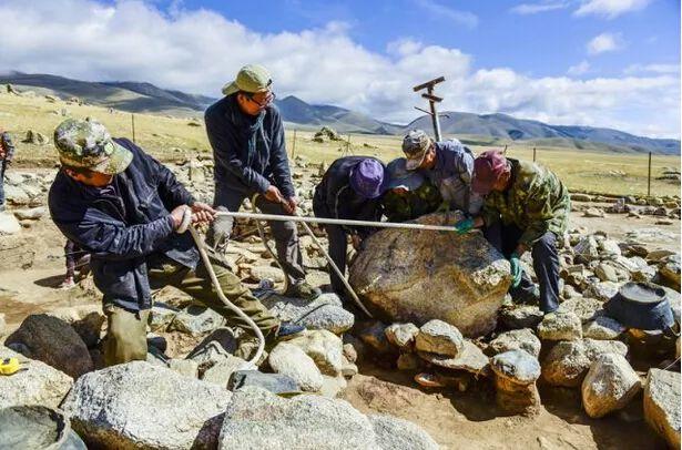 考古学者与当地的工人一起搬开遗址上的一块巨石。(新华社记者 沈桥摄)