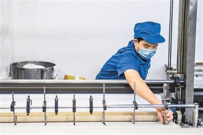 2月6日,海南澄迈欣龙控股公司工人在熔喷无纺布车间裁切生产出的过滤无纺布。蒲晓旭摄(新华社发)