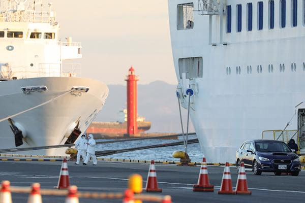 """2月6日,在日本横滨,身穿防护服的工作人员走过""""钻石公主""""号邮轮。新华社 图"""