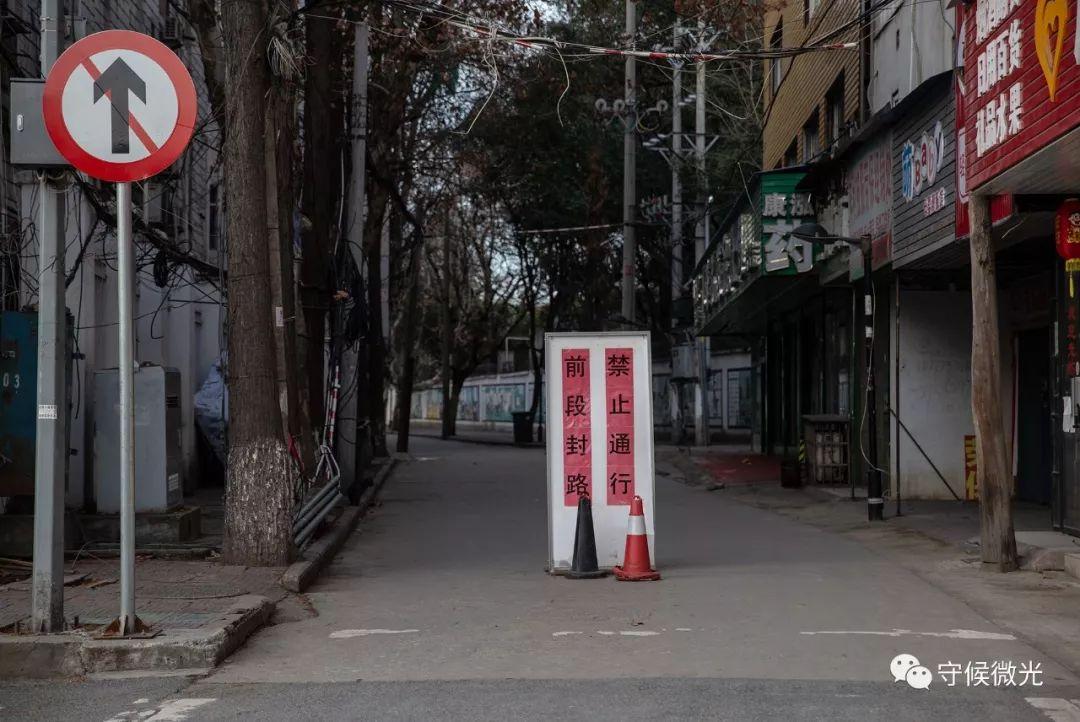 """2月17日,湖北省孝感市中央医院旁的路口,摆放了""""前段封路,不准大作""""的指使牌。中青报·中青网记者 李峥苨/摄"""