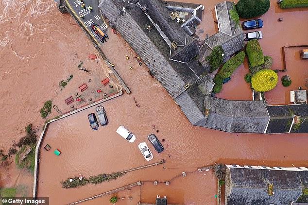 被洪水淹没的房屋和汽车(图片来源:《每日邮报》)