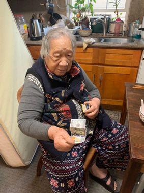 叶老太从钱夹取出一百美金。(受访者供图)
