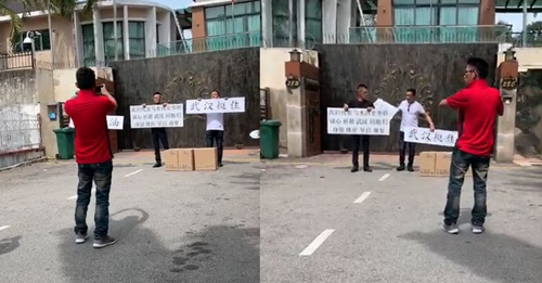 """男子还举着写有""""武汉挺住""""等字样的牌子(图源:马来西亚光华网)"""