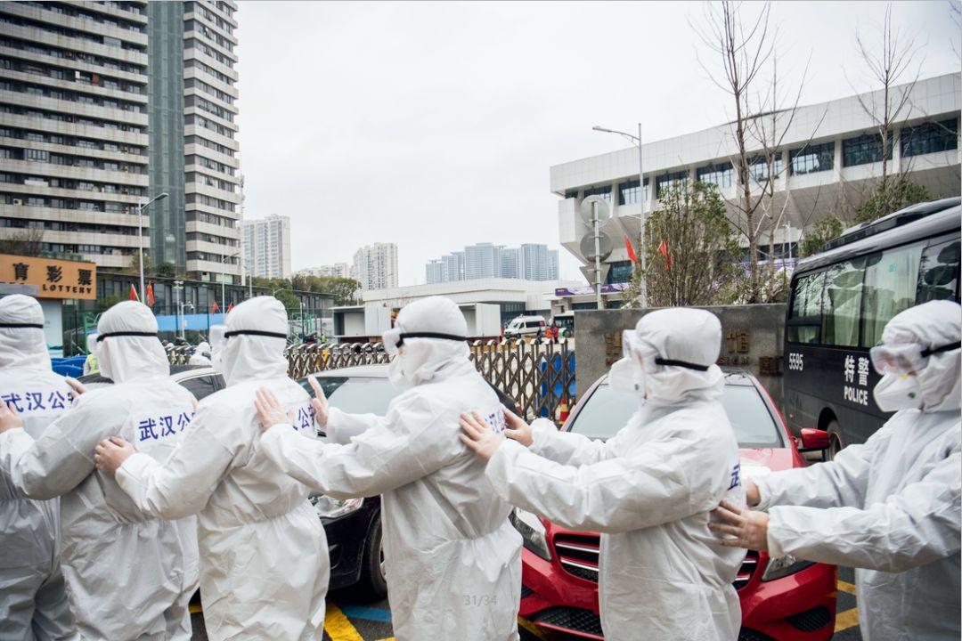 2月11日,一队准备进入武昌方舱医院执勤的民警在防护服外粘贴警察标志。摄影/湖北日报 魏铼