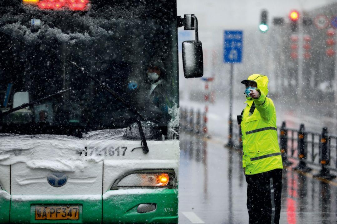 2月15日,武汉协和肿瘤医院改为定点医院收治病患,风雪中,医护、交警、公交及相关工作人员正在转运接收新冠肺炎患者。摄影/长江日报 陈卓