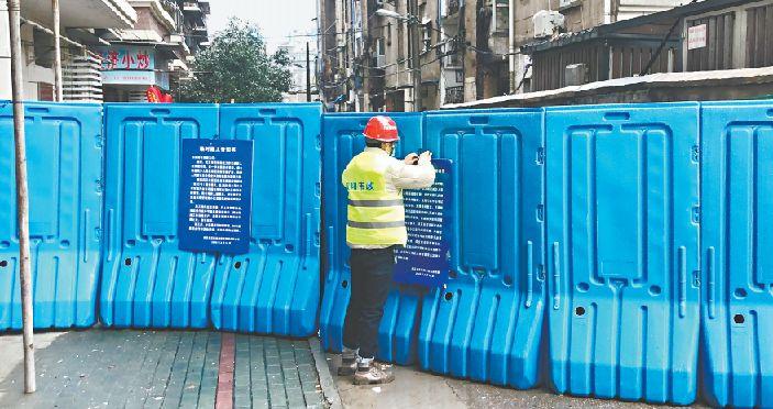 ▲汉阳市政施工人员在五麟里社区加固封闭挡板(图片源自武汉市政府网站)