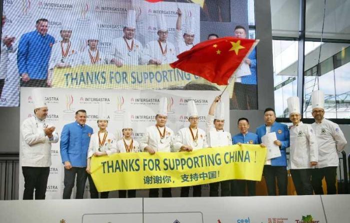 中国青年队上台领奖打出横幅,对组委会和各国朋友表示感谢。中国烹饪协会供图